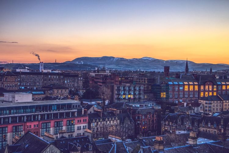 High angle shot of edinburgh townscape against sky at sunset