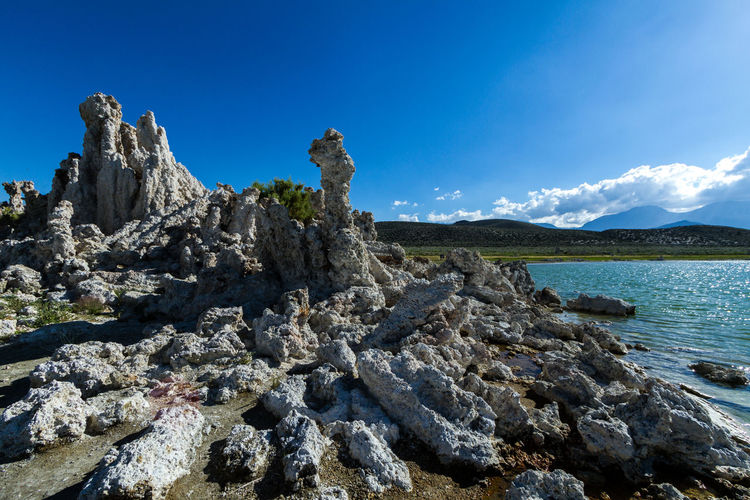 Scenic view of rocks against sea and blue sky