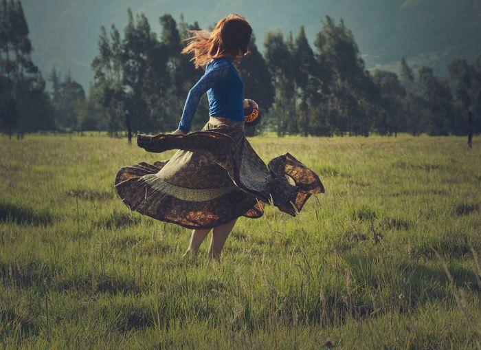 Woman dancing on grassy field