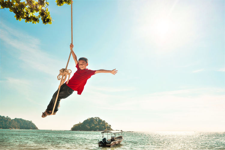 Boy swinging on rope swing over sea against sky during sunny day
