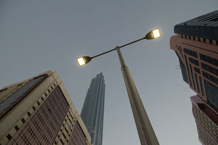 Low angle view of illuminated street light against buildings
