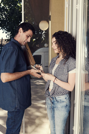 Woman signing on digital tablet held by delivery man