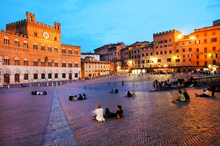 People relaxing by historic buildings at piazza del campo against sky during dusk