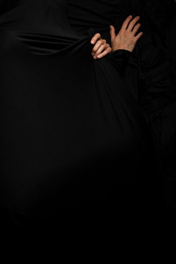 Midsection of woman standing against black background