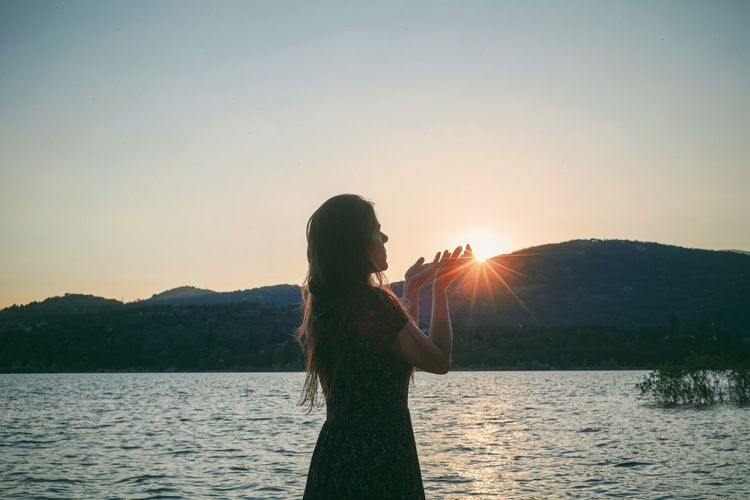 Side view of woman standing while gesturing against sky during sunset