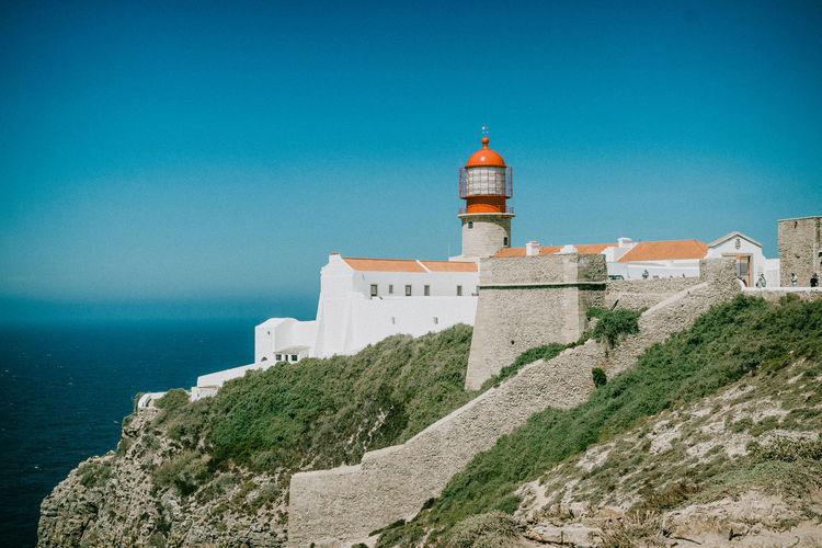 Lighthouse amidst buildings against blue sky