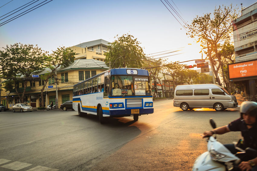 Bangkok, Thailand - March 2, 2017: Local bus and cars in traffic passes through a busy junction during sunset in Bangkok, Thailand. Sunlight Traffic Traffic Jam Traffic Signs Trafficlight Architecture Building Exterior Built Structure Car City Day Group Of People Junctionsquare Land Vehicle Men Mode Of Transportation Motor Vehicle Nature Outdoors People Public Transportation Real People Road Sky Street Sunbeam Sunrise Sunset Sunshine Traffic Arrow Sign Traffic Control Traffic Flow Traffic Light  Traffic Lights Traffic Sign Traffic Signal Trafficjam Trafficlights Transportation Tree