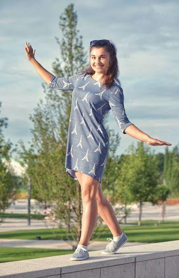 Beautiful woman wearing dress with eiffel tower pattern balancing on retaining wall