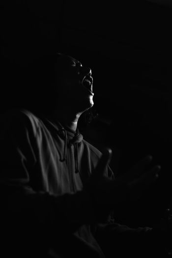 Low Angle View Of Man Shouting Against Black Background