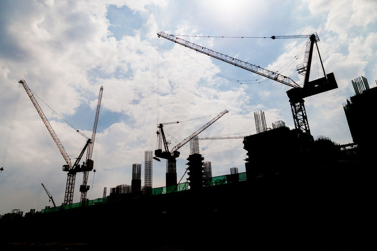 Construction site with cranes in silhouette Architecture Building Exterior Built Structure City Cloud - Sky Construction Site Crane - Construction Machinery Day Development Engineering Equipment Infrastructure Low Angle View Metal Columns No People Outdoors Silhoutte Sky