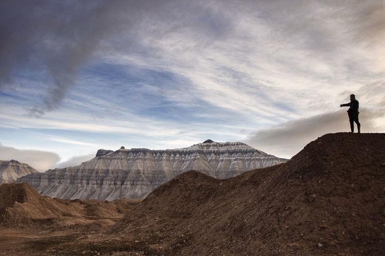 Man standing on mountain peak against sky