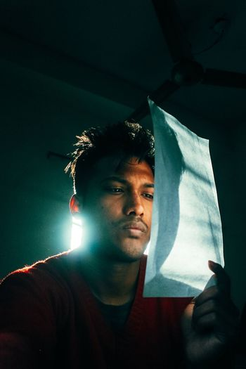 Thoughtful young man holding paper in darkroom