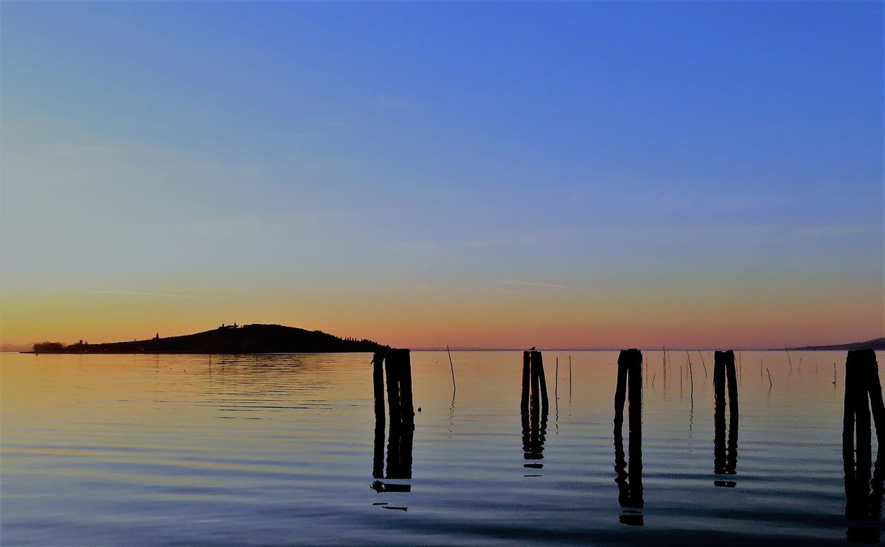 Silhouette Wooden Posts In Sea Against Clear Sky