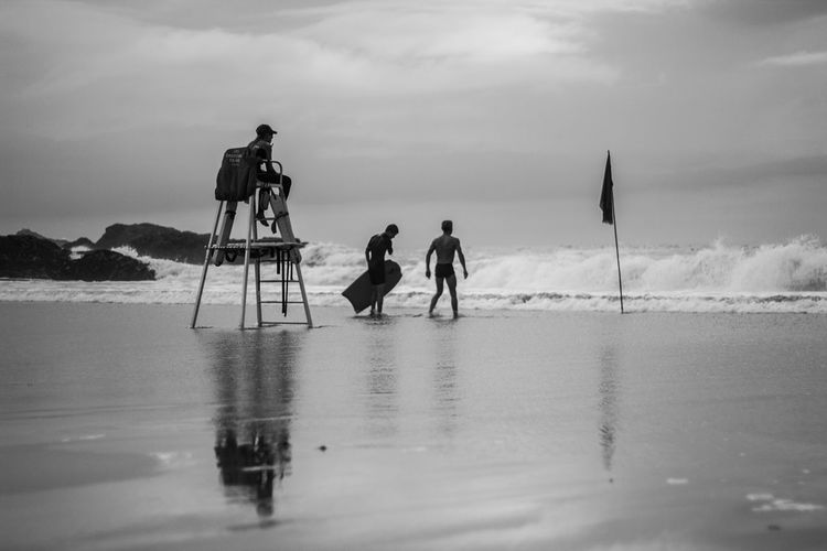 Men photographing at beach against sky