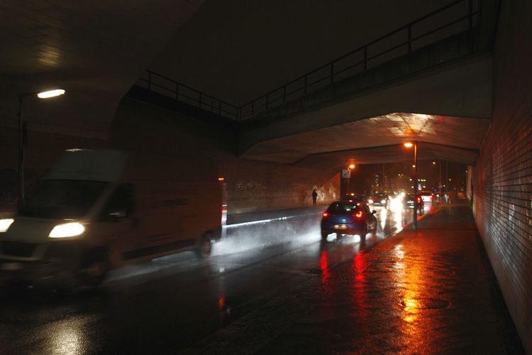 Illuminated wet street during rainy season at night