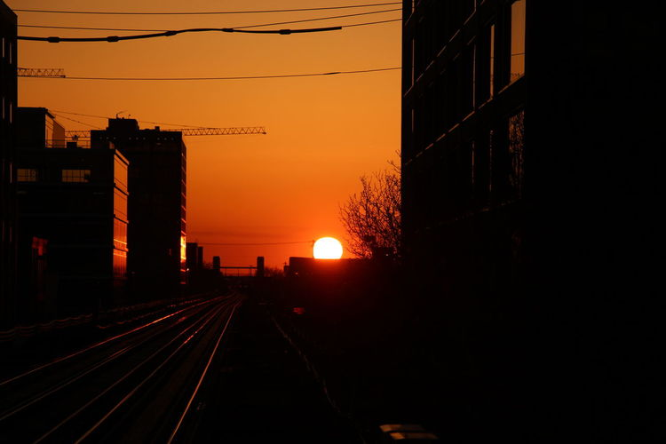Railroad tracks by silhouette buildings against sky during sunset