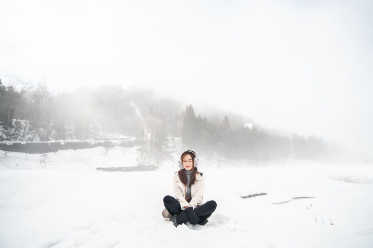 Snow Winter Cold Temperature One Person Sitting Full Length Young Adult Nature Day Mountain Adult Warm Clothing Leisure Activity Beauty In Nature Relaxation Cross-legged Looking At Camera Scenics - Nature