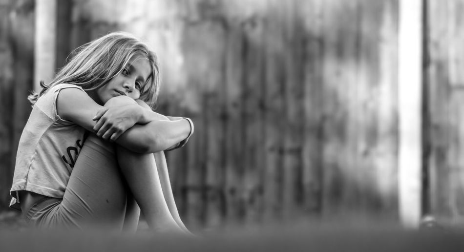 Portrait Of Thoughtful Girl Hugging Knees While Sitting Against Wall