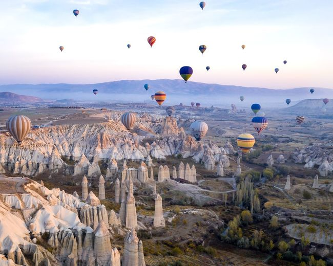 Hot air balloon flying over rocks against sky