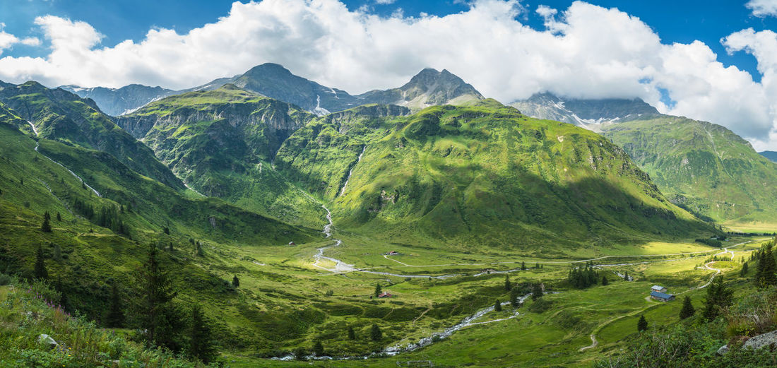 Green meadows and pastures surrounding alpine huts with mountains in the background, austria.