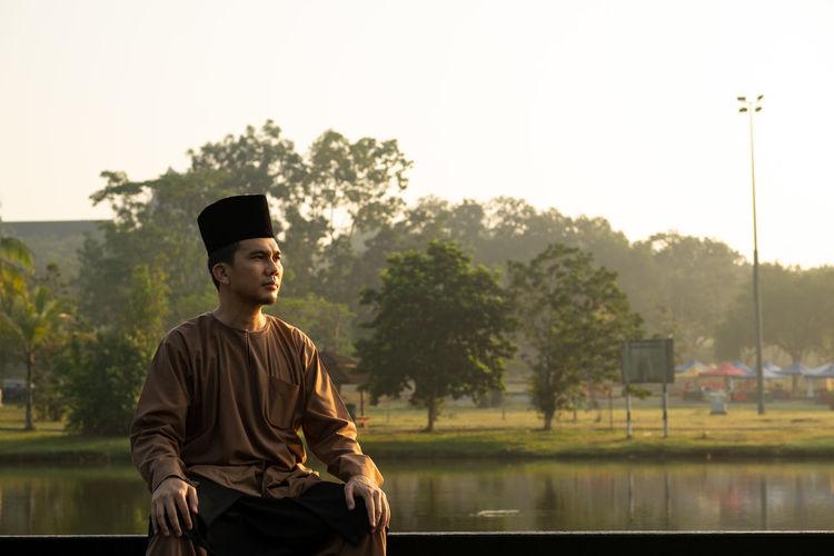Man Wearing Traditional Clothing While Sitting Against Lake During Sunset