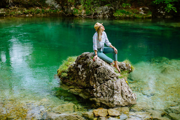Young Woman Sitting On Rock By Lake