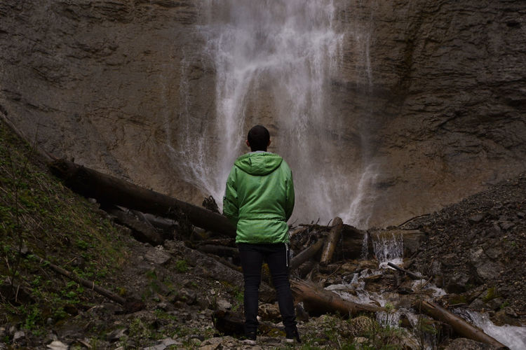 Rear view of man standing on rock looking at waterfall
