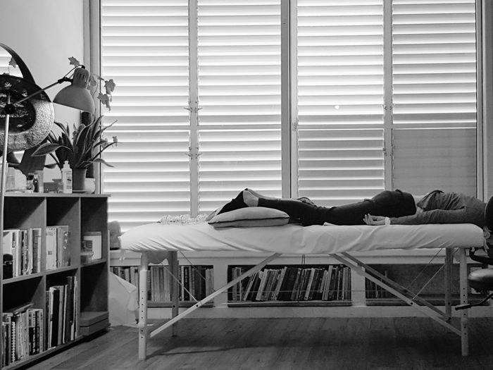 Low section of person sleeping on bed at home
