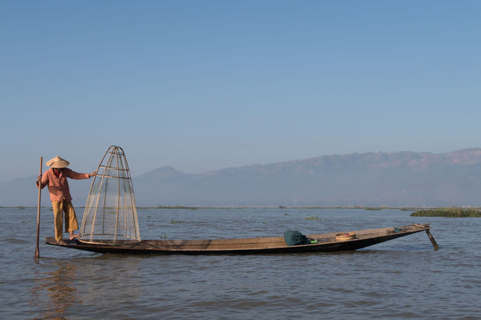 Balance Balancing Act Beauty In Nature Burma Cultures Day Fisherman Fishing Fishing Boat Fishing Net Fishing Tools Hat Inle Lake Lake Myanmar Nature Net Orange Clothes Outdoors People Scenics Sky Tradition Traditional Clothing Water