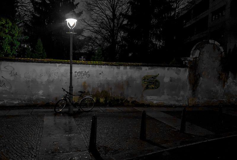 The Graveyard Wall Light Lantern Urban Wet Rainy Lowlight Iphoneedit Iapaward Iphoneshot Colorsplash Bike Darkness Dark darkness and light Wall Graveyard Street Light Bicycle Transportation Street Illuminated Night No People Tree City Outdoors