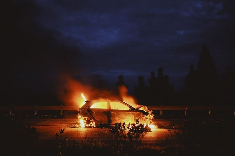 Burning fire in city against sky at night