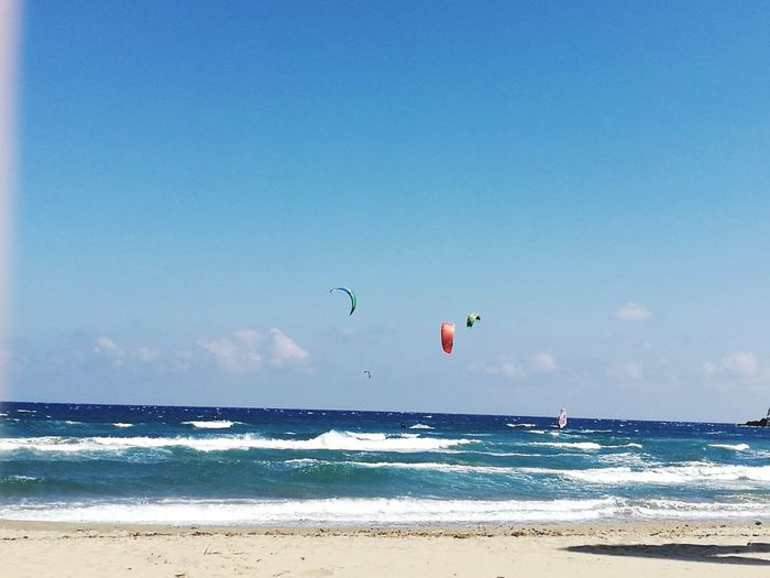 Flying Beach Sea Blue Water Beauty In Nature Nature Kiteboarding Outdoors Sky Day Scenics Parasailing No People Parachute