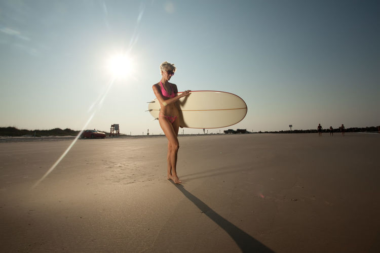 Mid adult woman with surfboard walking at beach against sky