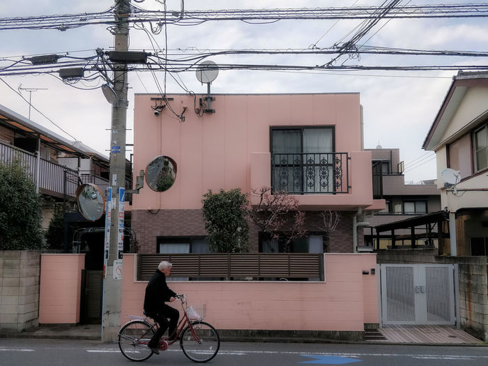 In Suginami ku. The sakura color house. Building Exterior Architecture Built Structure Bicycle Transportation City Mode Of Transportation Street Real People Day Outdoors Residential District One Person Electricity  Power Line  Riding Cable Japan Japanese  Tokyo Sakura
