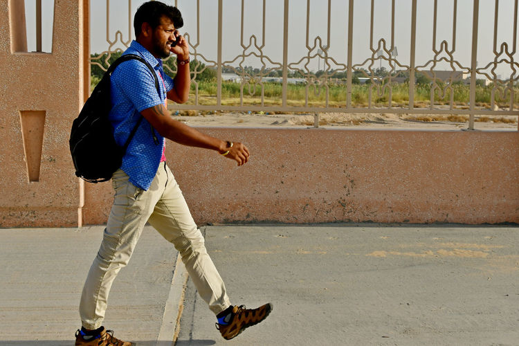 Young man using mobile phone while walking on footpath during sunny day