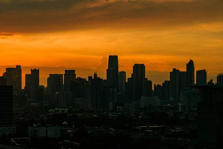 Silhouette buildings in city against orange sky
