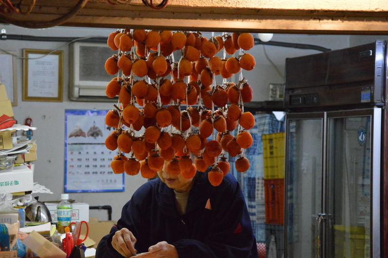 Woman by dried persimmons in store