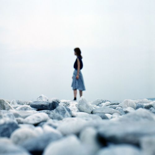 Surface Level Of Woman Standing On Pebbles At Beach Against Sky