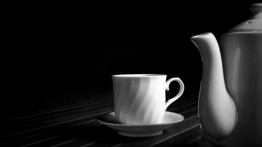 Vintage white ceramic coffee cup on wooden table and blurred teapot on foreground in black and white with dark tone style Low Key Dark Tone Blackandwhite Wooden Table Vintage Style Shape Selective Focus Blur Foreground Copy Space Ceramic Coffee Set Tea Set Container White EyeEm Selects Black Background Drink Tea - Hot Drink Coffee - Drink Table Saucer Coffee Cup Close-up Afternoon Tea Hot Drink Teapot Black Coffee Chinese Tea Tea Kettle