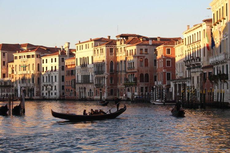 Gondolas on canal against sky