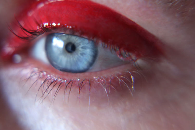 Cropped image of thoughtful woman with red eyeshadow