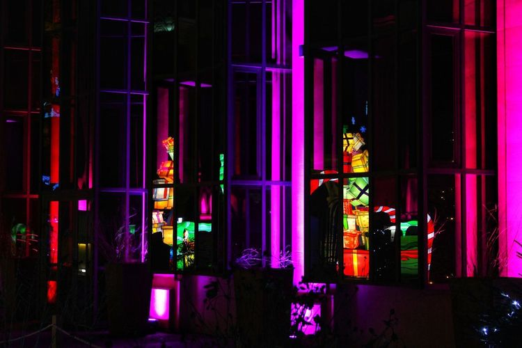 Multi colored illuminated building in city at night