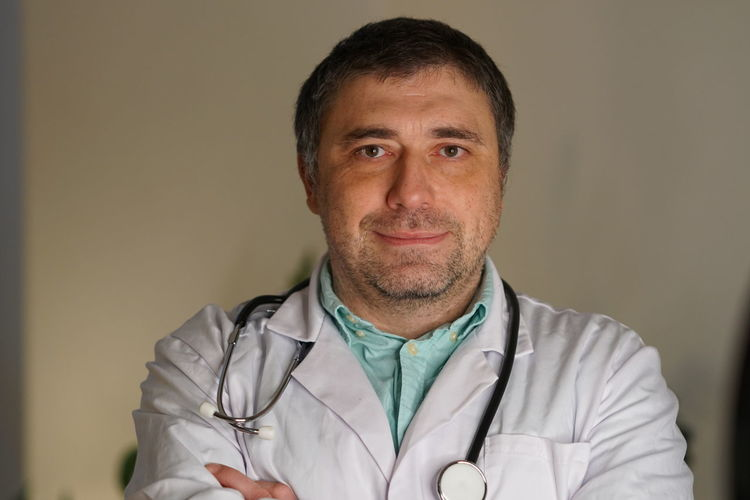 Portrait Of Smiling Mature Doctor Against Wall