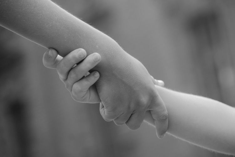 Cropped image of mother and daughter with holding hands