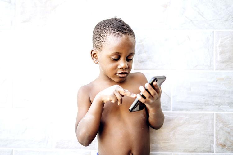 Full length of shirtless man using mobile phone