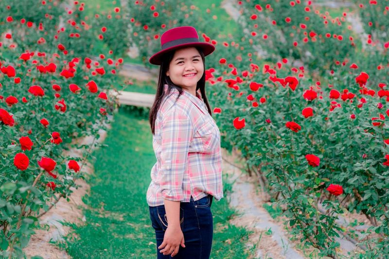 Portrait of smiling woman standing by red flowering plants