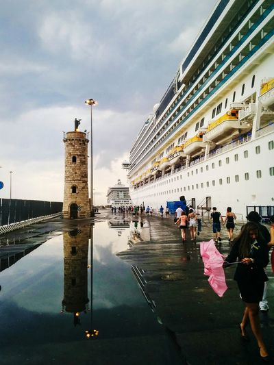 People walking on pier by cruise ship moored at harbor against sky
