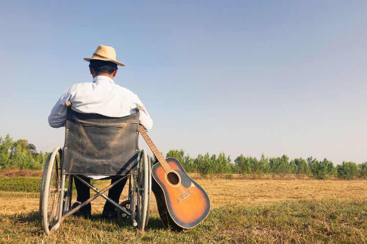 Rear view of man with guitar sitting on wheelchair against sky