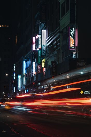 Illuminated Building Exterior Night Built Structure Road City Architecture Light Trail Transportation Street Mode Of Transportation Long Exposure Motion City Life City Street Speed Sign No People Building Blurred Motion