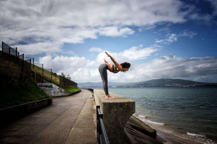 Side view of woman exercising by lake against cloudy sky